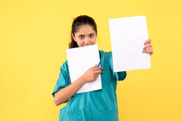 Vista frontal sorridente e linda médica segurando papéis sobre fundo amarelo