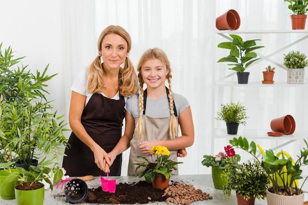 Vista frontal sorridente filha e mãe em estufa