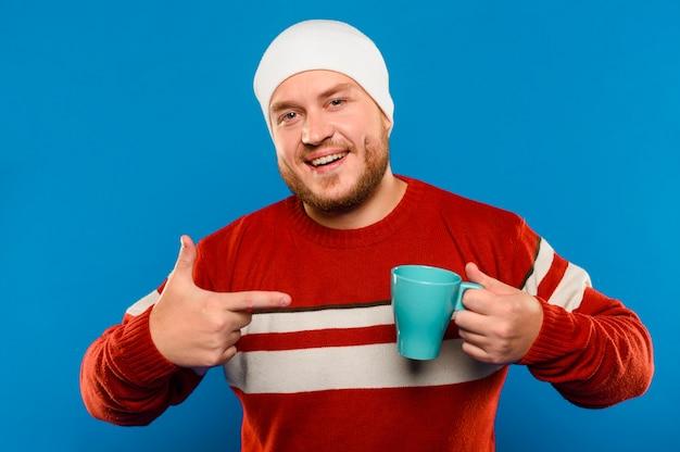 Vista frontal sorridente homem apontando para uma xícara de café