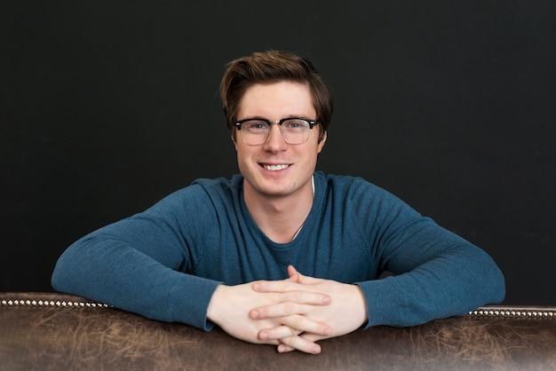 Vista frontal sorridente homem de blusa azul posando