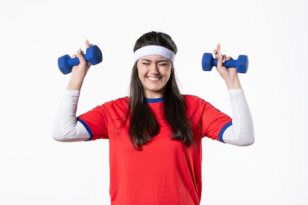 Vista frontal sorridente jovem mulher com roupas esportivas, malhando com halteres