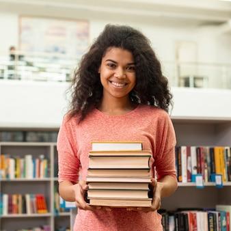 Vista frontal sorridente menina segurando a pilha de livros