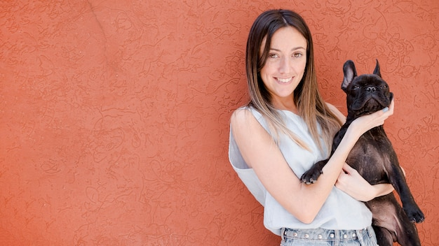 Vista frontal sorridente menina segurando seu cachorro