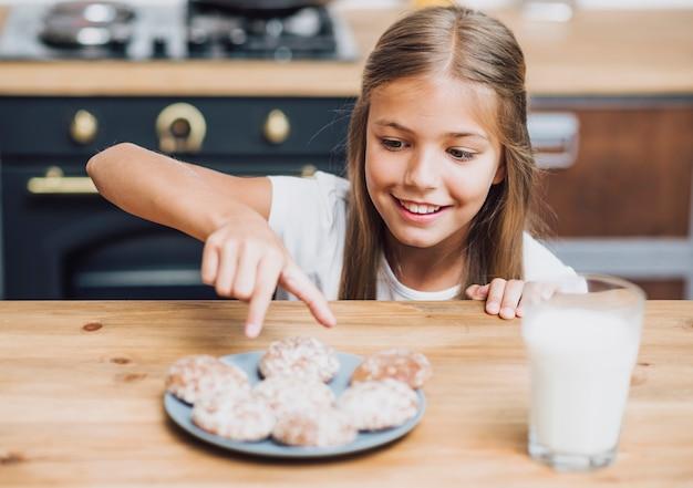 Vista frontal sorridente menina tomando um delicioso biscoito
