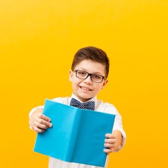 Vista frontal sorridente menino apresentando livro