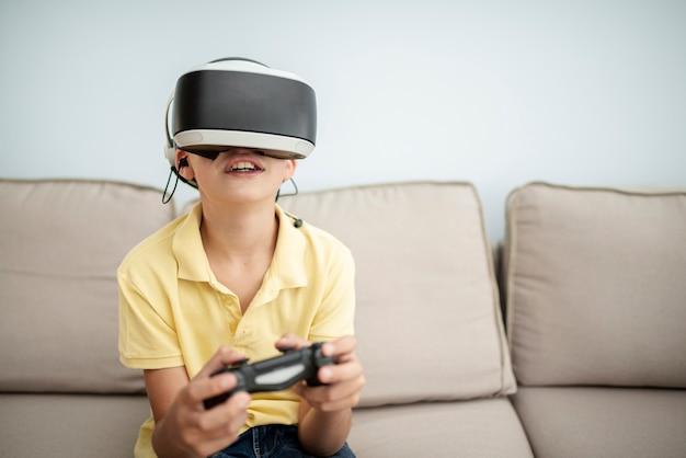 Vista frontal sorridente menino brincando com óculos vr