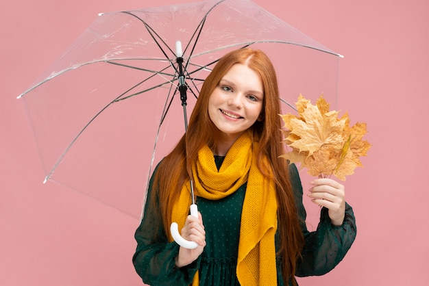 Vista frontal sorridente mulher segurando guarda-chuva