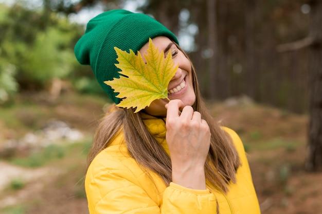 Vista frontal sorridente mulher segurando uma folha amarela