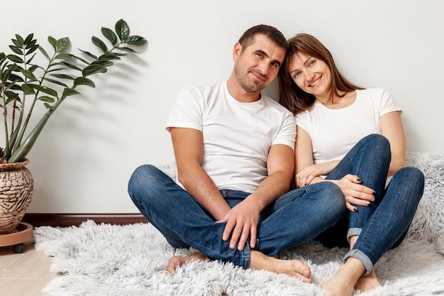 Vista frontal, sorrindo casal sentado no chão