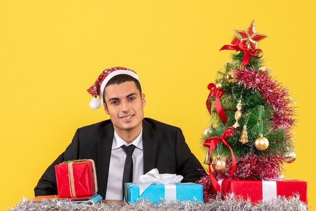 Vista frontal sorrindo homem com chapéu de papai noel sentado à mesa com presentes árvore de natal e presentes