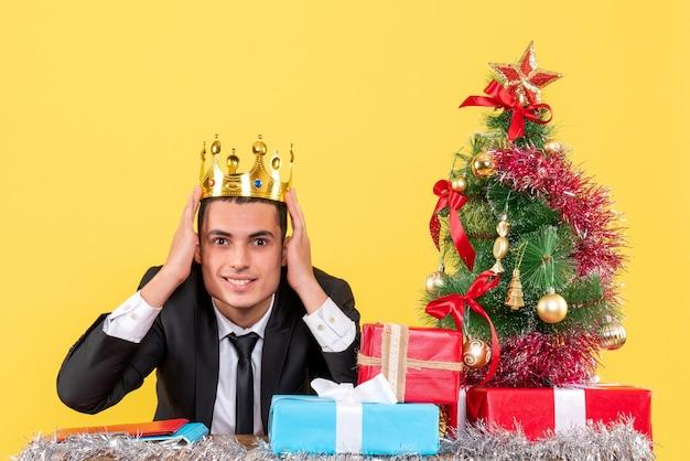 Vista frontal sorrindo homem com coroa sentado à mesa árvore de natal e presentes