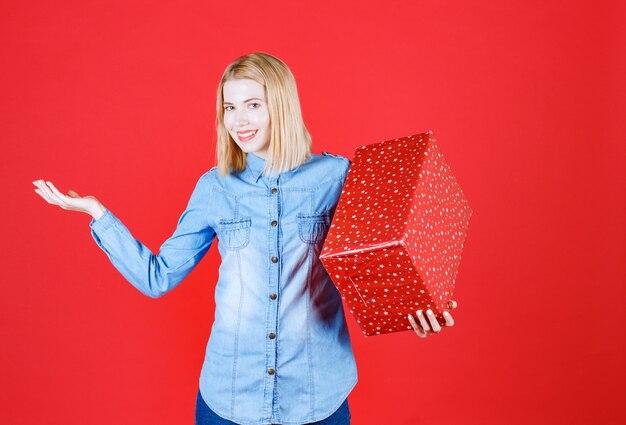 Vista frontal sorrindo jovem segurando a caixa de presente e abrindo a mão