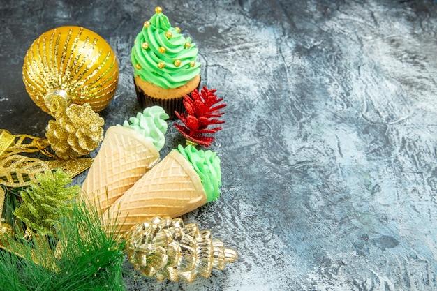 Vista frontal, sorvetes, árvore de natal, cupcake, enfeites de natal em fundo cinza