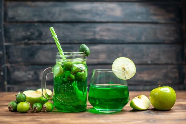 Vista frontal, suco de feijoa verde com maçã verde na foto colorida de fruta em barra escura.
