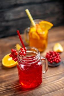 Vista frontal, suco de frutas frescas, bebidas de laranja e cranberry dentro de latas na mesa de madeira marrom.