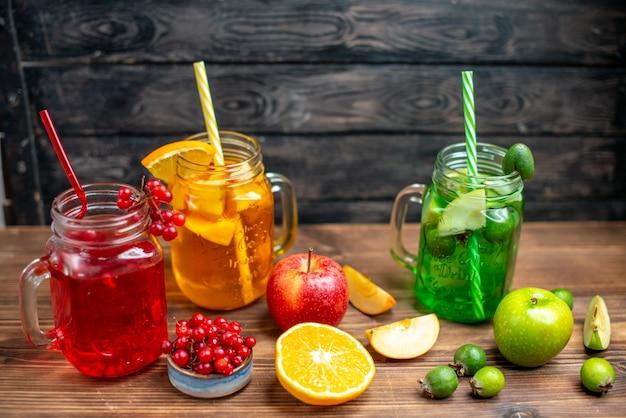 Vista frontal suco de frutas frescas, feijoa de laranja e bebidas de cranberry dentro de latas na mesa marrom.