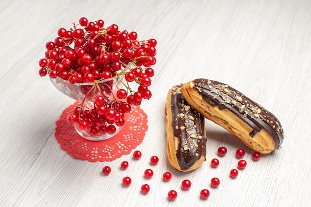 Vista frontal superior de groselha em um copo de cristal no guardanapo de renda oval vermelha e éclairs de chocolate na mesa de madeira branca