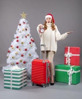 Vista frontal surpreendendo a garota loira com chapéu de papai noel segurando um despertador vermelho perto da árvore de natal