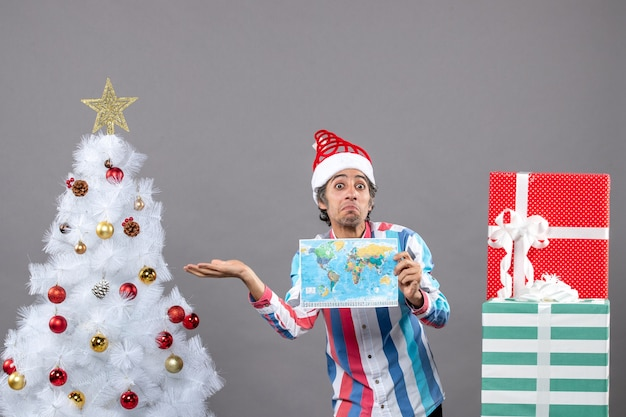 Vista frontal surpreendendo o homem com chapéu de papai noel espiral apontando para a árvore de natal branca