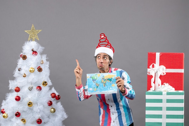 Vista frontal surpreendendo o homem com chapéu de papai noel espiral apontando para a árvore de natal