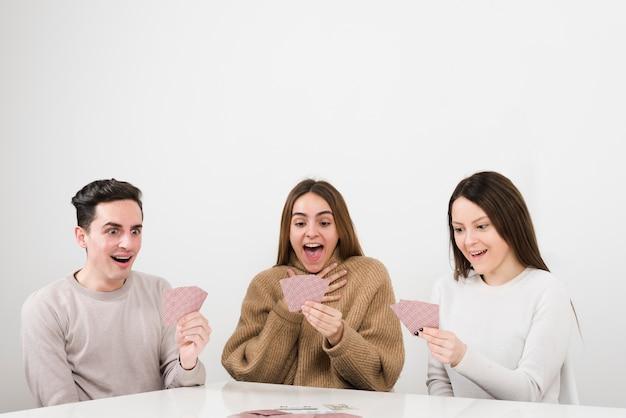 Vista frontal surpreendeu amigos jogando cartas jogo