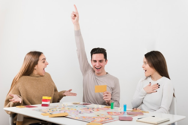 Vista frontal surpreendeu amigos jogando um jogo de tabuleiro