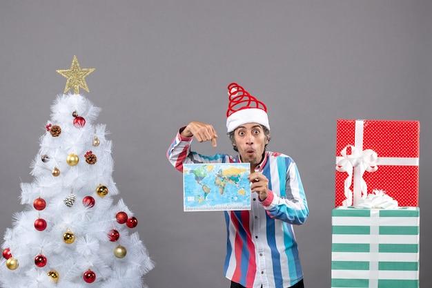 Vista frontal surpreendeu o homem com chapéu de papai noel com mola espiral e camisa listrada, mostrando o mapa perto da árvore de natal branca e presentes com espaço de cópia