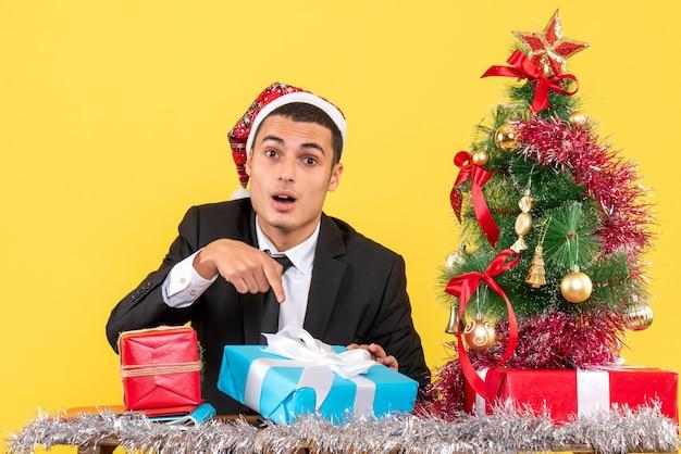 Vista frontal surpreendeu o homem com chapéu de papai noel sentado à mesa mostrando seu presente e árvore de natal