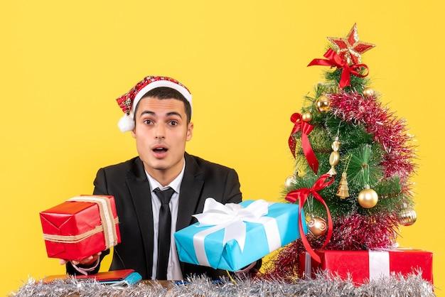 Vista frontal surpreendeu o homem com chapéu de papai noel sentado à mesa segurando presentes, árvore de natal e presentes