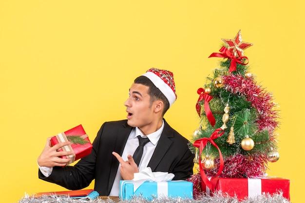 Vista frontal surpreendeu o homem com chapéu de papai noel sentado à mesa segurando uma árvore de natal e presentes