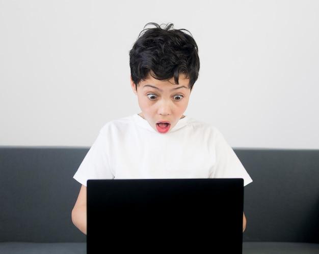 Vista frontal surpreendeu o menino com laptop