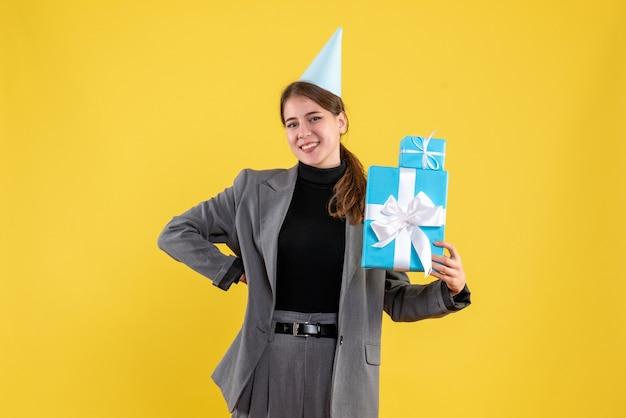 Vista frontal surpresa garota com chapéu de festa segurando presentes de natal colocando a mão