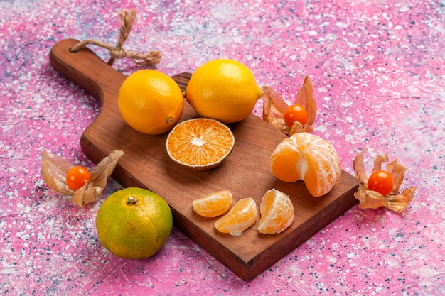 Vista frontal tangerinas frescas azedas com limões no fundo rosa.