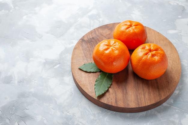 Vista frontal, tangerinas frescas e suculentas, cítricos suaves, cor de laranja na mesa branca, frutas cítricas tropicais exóticas