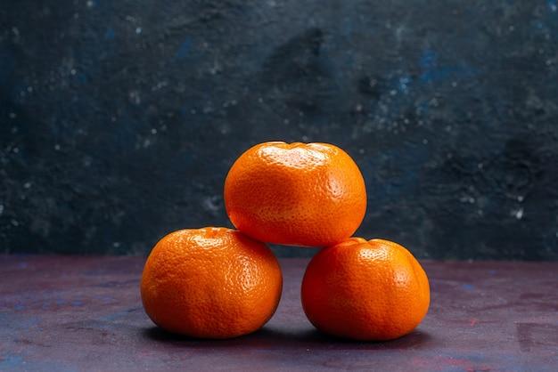 Vista frontal, tangerinas frescas e suculentas de cor laranja na mesa escura, frutas cítricas tropicais exóticas de laranja