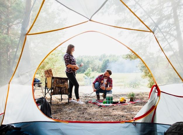 Vista frontal tenda e casal cozinhar