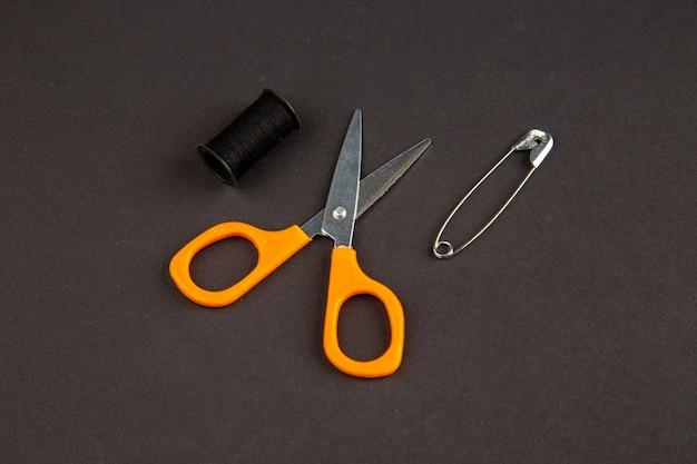 Vista frontal, tesoura laranja na superfície escura, cor da faca, foto escura, corte nítido
