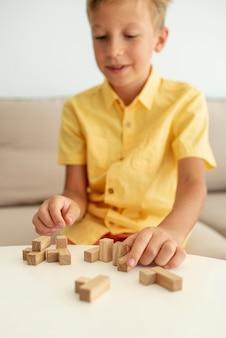 Vista frontal turva garoto brincando com peças de jenga