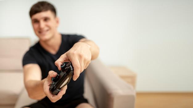 Vista frontal turva menino brincando com um controlador