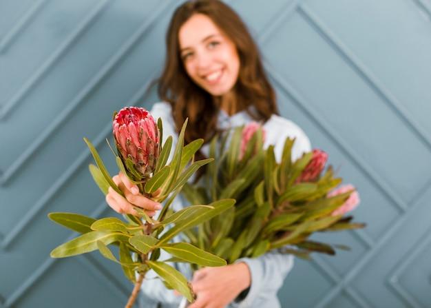 Vista frontal turva mulher posando com flores
