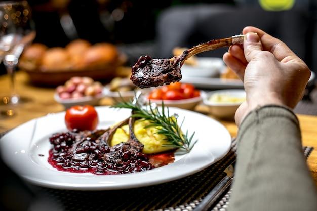 Vista frontal, um homem come costelas de cordeiro fritas em molho de romã
