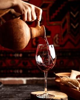 Vista frontal, um homem derrama de um jarro em um copo de vinho tinto