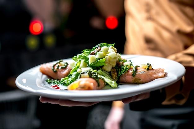 Vista frontal, um homem segura um prato com salada de legumes com peixe vermelho com verduras