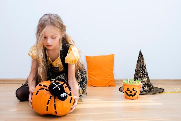 Vista frontal uma menina sentada no chão no dia das bruxas