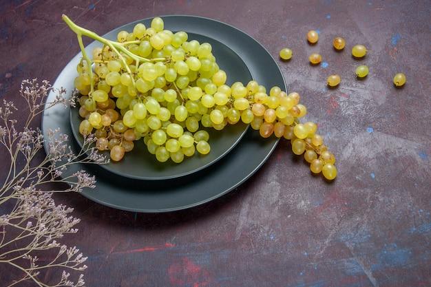 Vista frontal uvas frescas maduras uvas verdes na superfície escura vinho uvas frescas plantas de árvores maduras