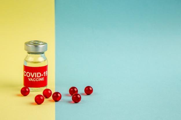 Vista frontal vacina contra coronavírus com pílulas vermelhas em cor de fundo amarelo-azul vírus pandêmico laboratório de saúde covid- hospital ciência droga