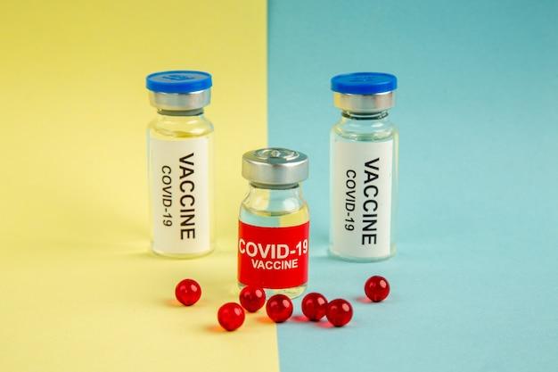 Vista frontal vacina contra coronavírus com pílulas vermelhas sobre fundo amarelo-azul vírus hospitalar cor pandêmica laboratório covid-ciência droga
