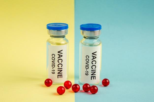 Vista frontal vacina de coronavírus com pílulas vermelhas em cores de fundo amarelo-azul vírus pandêmico laboratório de saúde covid- hospital ciência droga
