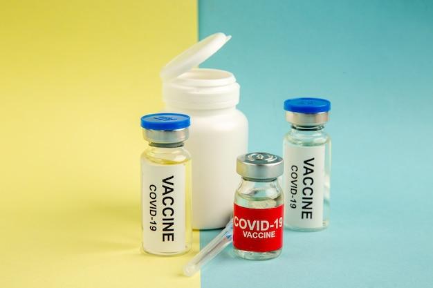 Vista frontal vacinas contra coronavírus com injeção em fundo amarelo-azul laboratório hospital vírus covid- ciência saúde pandemia cor droga