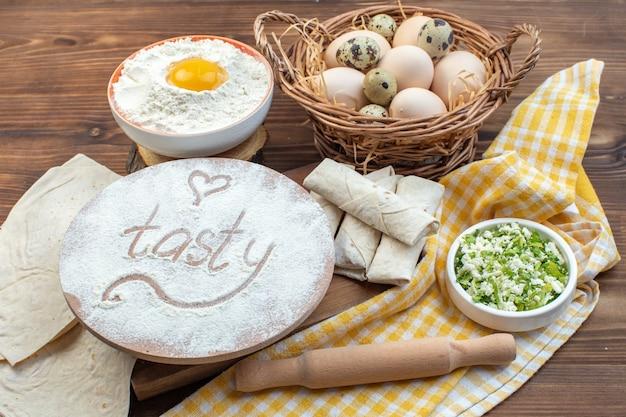 Vista frontal verdes pita rolos com ovos e farinha no fundo marrom cozinhar comida assar bolo pastelaria cozinha pão de carne